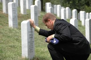 Jerry's son, Craig, kneels before his father's memorial stone, during the 40th Memorial Service in Arlington Nat'l Cemetery, 8/20/2009