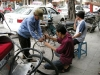 Cyclos compete with motorbikes in busy Hanoi -- here a cyclo owner gets a quick fix for his tire.