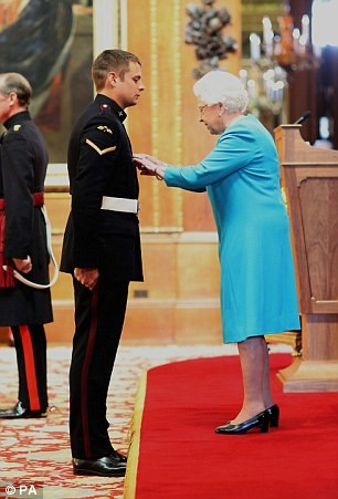 Her Majesty Queen Elizabeth presents British Paratrooper Lance Corporal Joshua Leakey with the Victoria Cross, awarded for valor in combat.